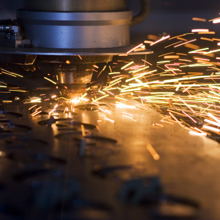 Laser cutting metal sheet in factory with sparks flying around